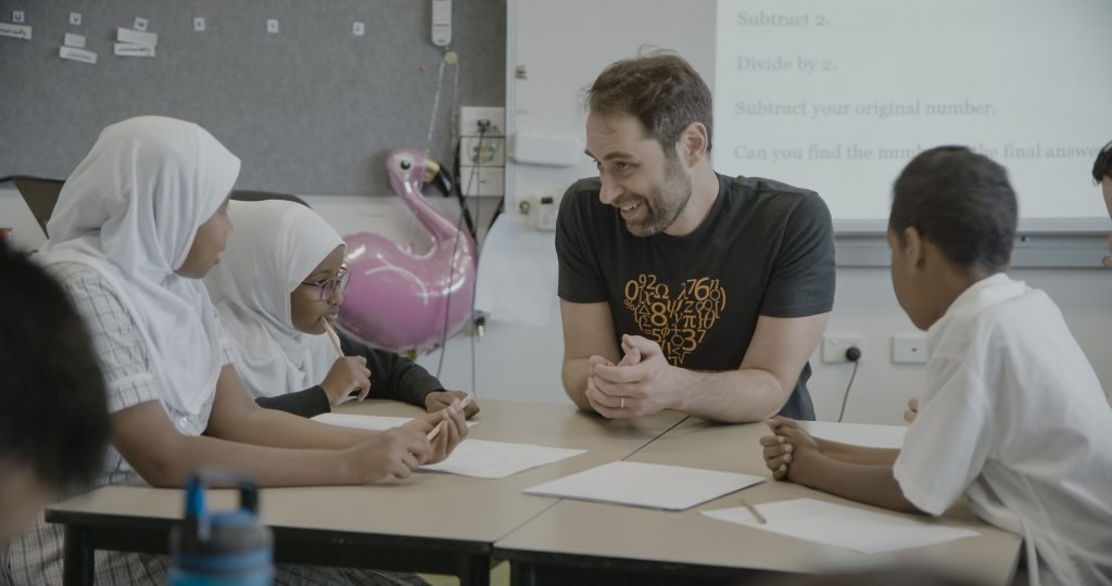 A smiling Dan Finkel sits at a classroom table with three students.