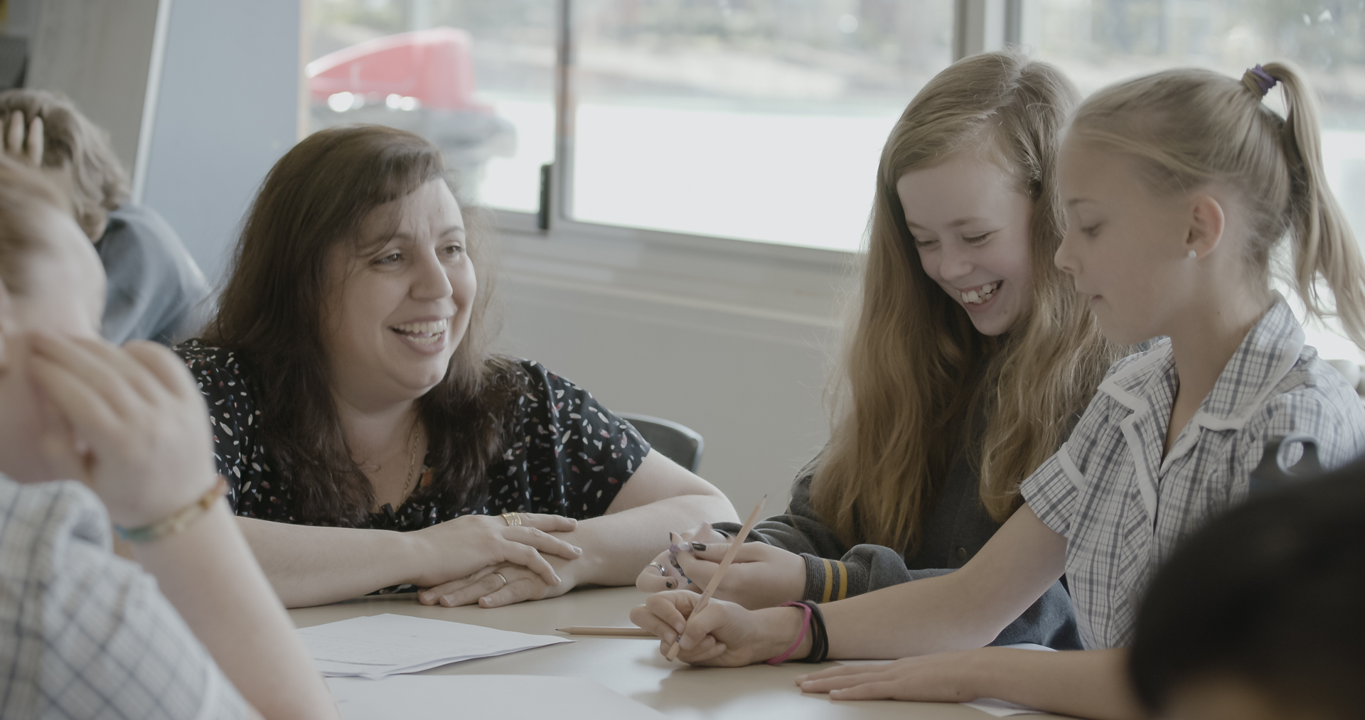 Two girls sit working at a table with a female teacher at their eye level, smiling at them with a big grin as they work. One of the students is also smiling wide.