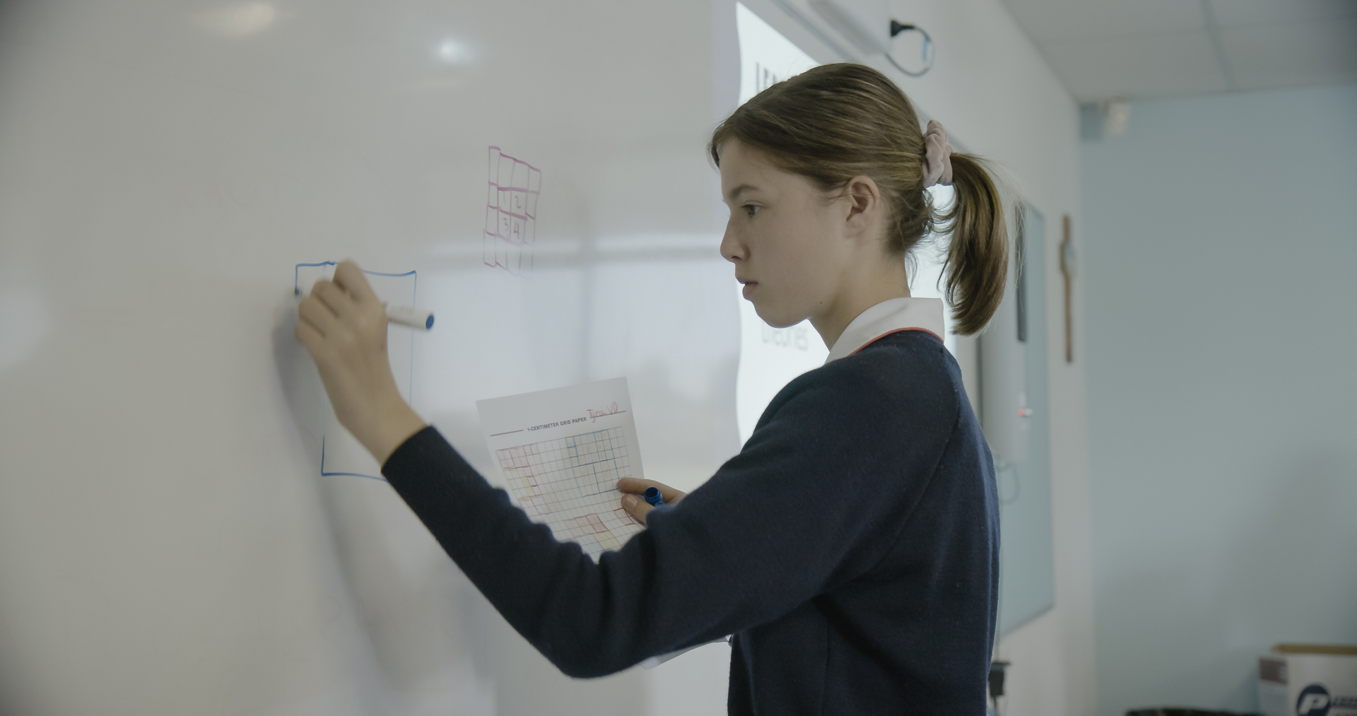 One girl draws a shape on the whiteboard, her face intense with focus.