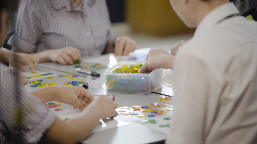 Students use counters in the classroom to help solve maths problems.