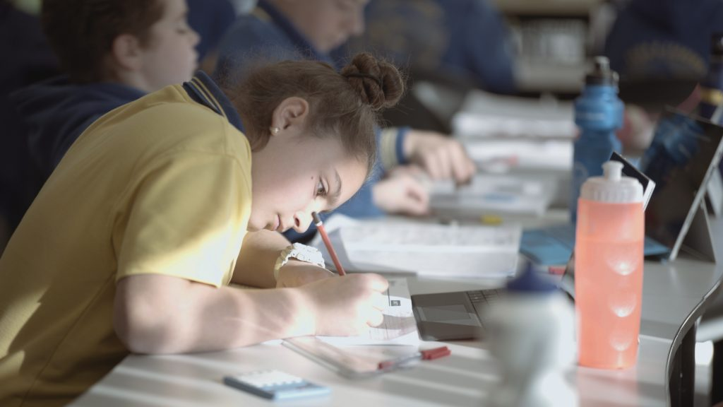 A girl is concentrating on her workbook as she writes pencil to paper.