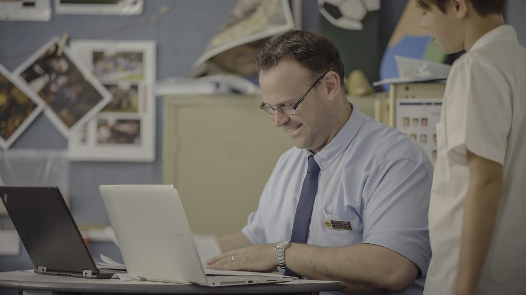 A teacher sits at a desk at the front of the classroom with his own laptop and a student's laptop. The student stands next to him looking on. The teacher is smiling as the pair converse in their feedback session.